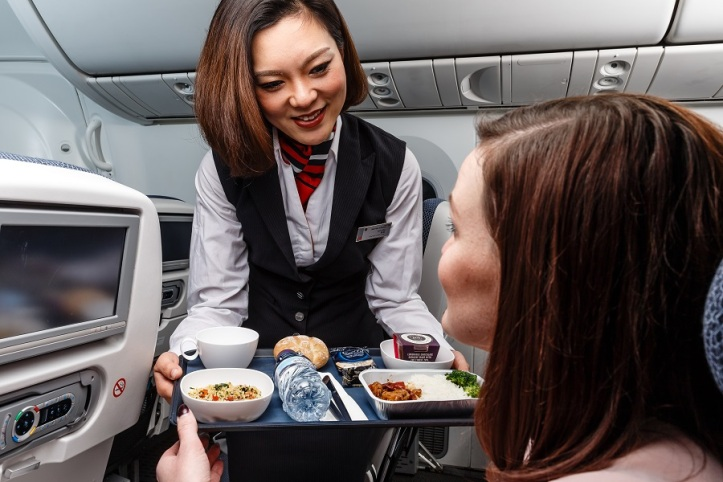 British Airways' new World Traveller catering - cabin crew serve main meal on flights to the Far East